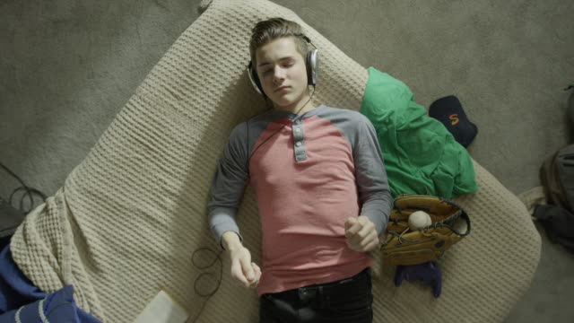 Medium high angle shot of boy listening to music on bed / Cedar Hills, Utah, United States