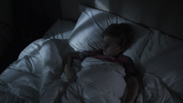 Medium high angle time lapse shot of boy having nightmares in bed / Cedar Hills, Utah, United States