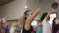 Medium high to low angle shot of people dancing in exercise class / Orem, Utah, United States
