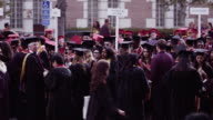 medium lens camera pans and shifts focus through graduates who wait for procession