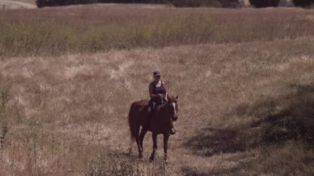Medium long lens, camera pans with Karen riding through pasture. Karen turns horse and rides towards camera into close shot