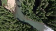 'Medium Long Shot aerial pan-left tracking-right-A dense evergreen forest surrounds a river in Alaska. / Alaska, USA'