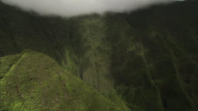 Medium Long Shot aerial push-in tracking-left - Fog drifts over lush mountains with gulleys on Hawaii's Kauai island. / Hawaii, USA