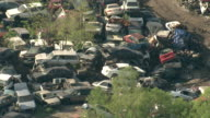 Medium Long Shot aerial push-out zoom-out - Wrecked cars fill a junkyard. / New Orleans, Louisiana, USA