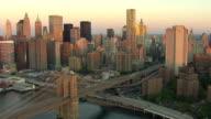 Medium Long Shot  aerial tracking-left - Skyscrapers tower along the East River near the Brooklyn Bridge. /  New York City