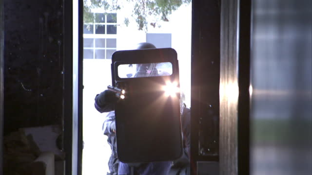 Medium Long Shot hand-held - Riot police enter a building with shields, flashlights and weapons. / Virginia, USA