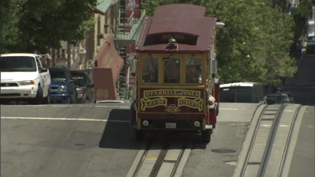 Medium Long Shot hand-held zoom-in - A cable car passes other traffic in San Francisco. / San Francisco, California, USA