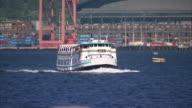 Medium Long Shot pan-right - A ferry cruises in a harbor. / North Carolina, USA