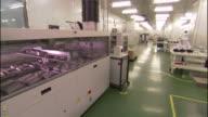 Medium Long Shot pan,right , Robots and technicians work on a factory floor. / California