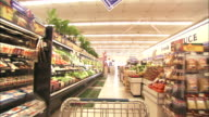 Medium Long Shot push-in - A shopping cart moves through the produce department in a grocery store