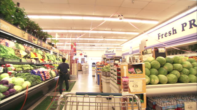 Medium Long Shot push-out - A shopping cart backs down an aisle in the produce department in a supermarket