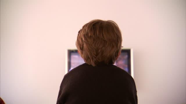 Medium Long Shot static - A boy watches television.