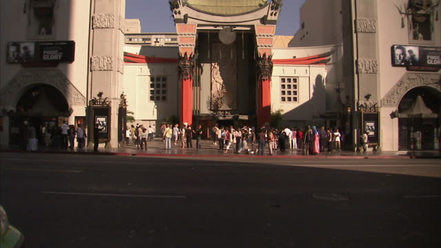 Medium Long Shot static - A city bus passes the entrance of Grauman's Chinese Theatre on Hollywood Boulevard. / Los Angeles, California, USA