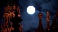 Medium Long Shot static - A full moon illuminates intricate Gothic spires in London. / London, UK