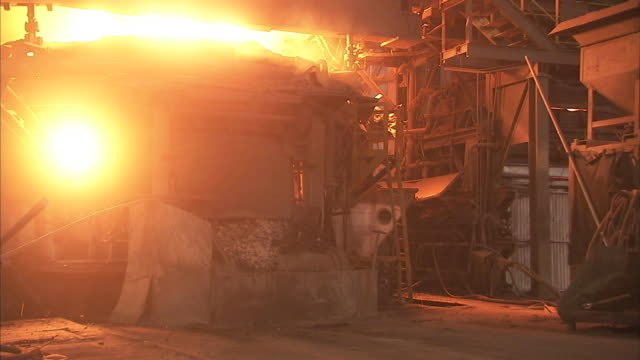 Medium Long Shot static - A steel mill furnace emits sparks and billowing flames / Claymont, Delaware