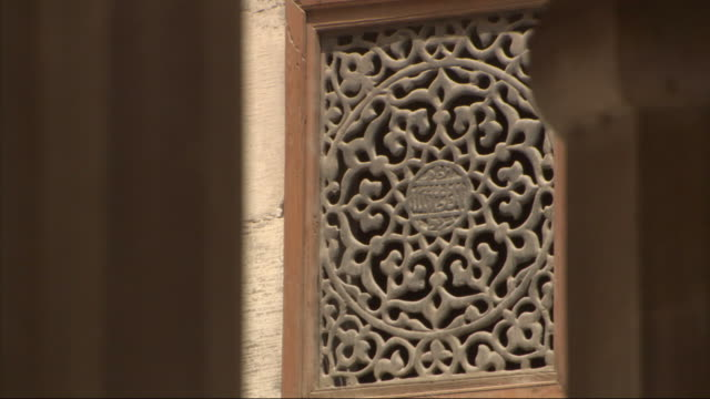 Medium Long Shot, static - An ornate grate is embedded in a building's facade / Egypt