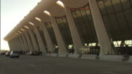 Medium Long Shot static - Cars drive past the terminal at Dulles International Airport. / Dulles, Virginia, USA