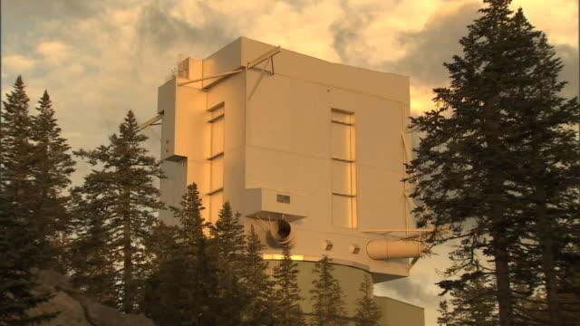 Medium Long Shot static - Evergreens surround a telescope / USA