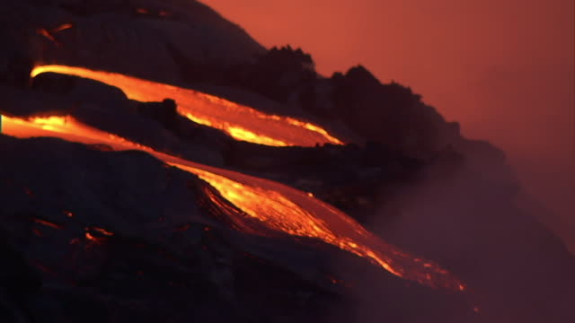 Medium Long Shot static - Glowing lava flows from a volcanic eruption on Hawaii's Big Island. / Hawaii, USA
