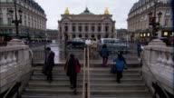 Medium Long Shot static - Traffic and pedestrians speed past the Palais Garnier in Paris. / Paris, France