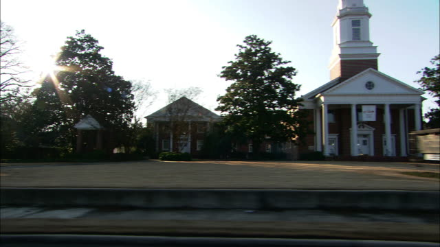 Medium Long Shot tracking-left - Sun rays beam behind a church steeple and houses in a Georgia neighborhood. / Georgia, USA