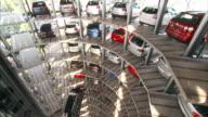 Medium Long Shot_crane - A hydraulic arm lifts a car into position in a tower garage. / Wolfsburg, Germany