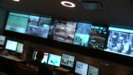 Medium Long Shot_tracking-left zoom-out - Situation monitors surround police dispatchers in a New York City police control room. / New York City, New York, USA