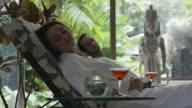 Medium low angle panning shot of couple relaxing in spa / Arenal, La Fortuna, Costa Rica