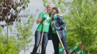Medium low angle panning shot of volunteers posing with shovels / Cedar Hills, Utah, United States