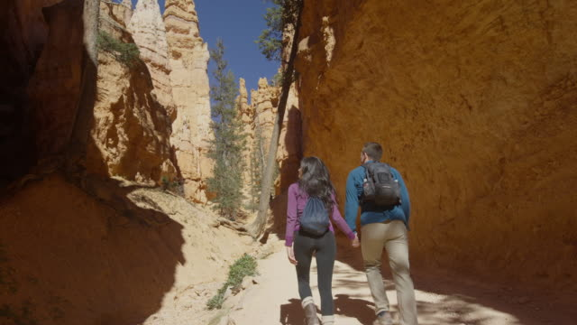Medium low angle shot of couple hiking in canyon / Bryce Canyon National Park, Utah, United States