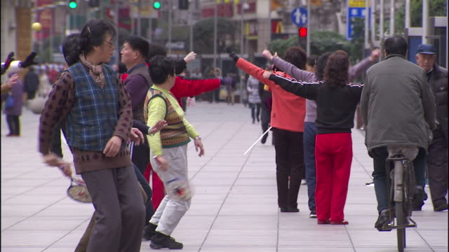 Medium pan,left , Pedestrians pass a group of street performers using fans and balls. / Shanghai, China
