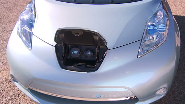 Medium pan,left push,in tilt,down tracking,left , A Nissan Leaf features electrical ports under the front hood. /