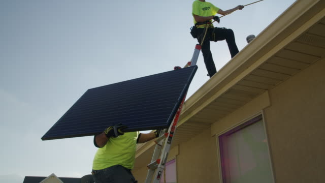 Medium panning low angle shot of workers carrying solar panel on roof / Mapleton, Utah, United States