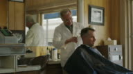 Medium panning shot of barber cutting hair of customer / Pleasant Grove, Utah, United States