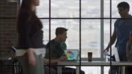 'Medium panning shot of business people talking in meeting / Lehi, Utah, United States'