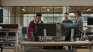 Medium panning shot of business people working together in office / Lehi, Utah, United States