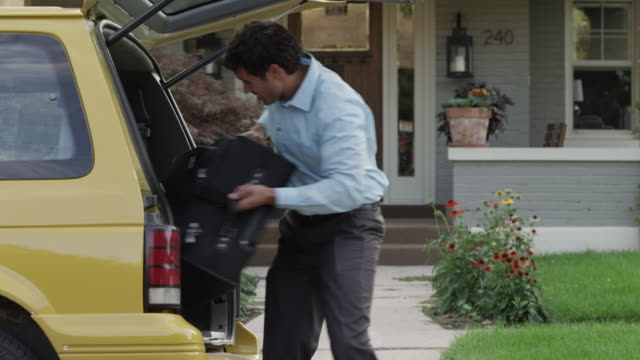 Medium panning shot of businessman loading suitcase into hatchback of minivan taxi / Provo, Utah, United States