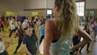 Medium panning shot of fitness instructor leading exercise class / Orem, Utah, United States