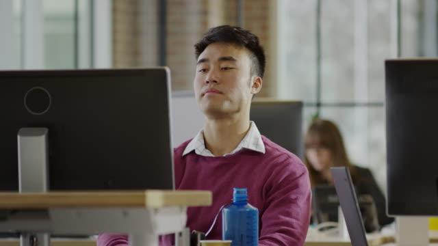 Medium panning shot of frustrated businessman working at desk / Lehi, Utah, United States