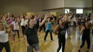Medium panning shot of instructor running into middle of fitness class / Orem, Utah, United States
