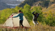 Medium panning shot of man running from insect while camping / American Fork Canyon, Utah, United States