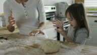 Medium panning shot of mother and daughter baking cookies in kitchen / Provo, Utah, United States