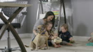 Medium panning shot of mother sitting on floor playing with children and dog / Cedar Hills, Utah, United States