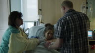 Medium panning shot of nurse and parents of newborn in hospital / Midvale, Utah, United States