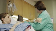Medium panning shot of nurse checking vital signs of pregnant patient / Midvale, Utah, United States