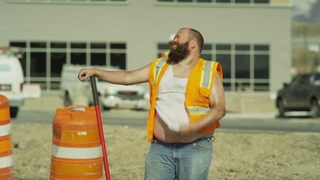 Medium panning shot of overweight construction worker sweating / Lehi, Utah, United States