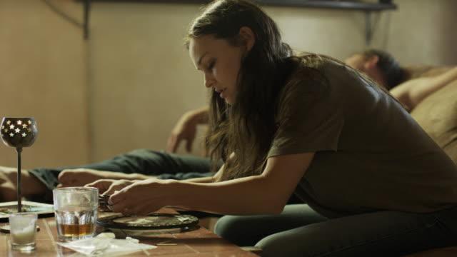 Medium panning shot of woman arranging cocaine into lines / Springville, Utah, United States