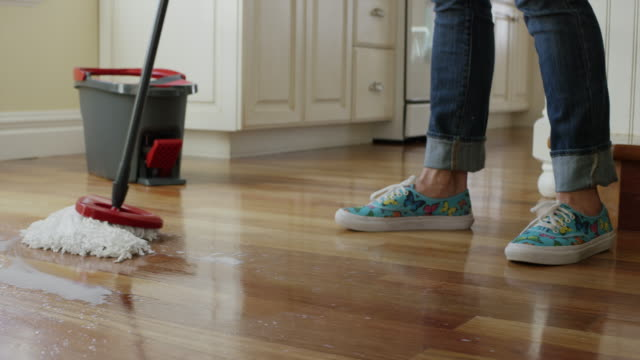 'Medium panning shot of woman mopping kitchen floor / Cedar Hills, Utah, United States'