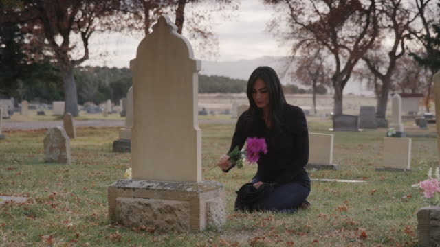 Medium panning shot of woman placing bouquet on gravestone / Spring City, Utah, United States