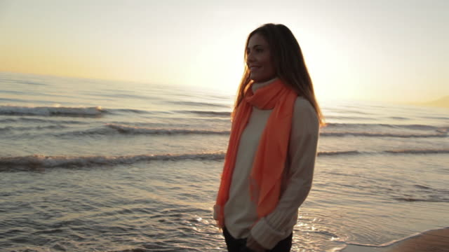 Medium panning shot of woman walking on beach/Marbella region, Spain